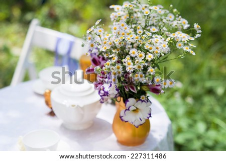 Nicely decorated outdoor setting with a bunch of flowers in vase placed on a table - stock photo