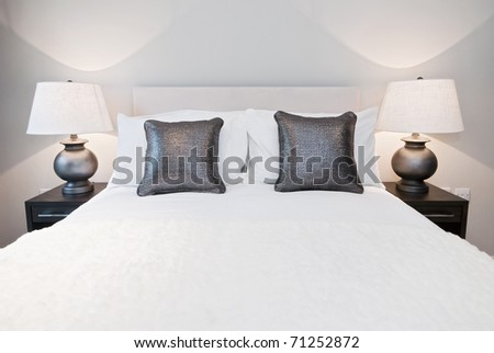 nicely done double bed with metallic effect cushions and other accessory - stock photo
