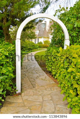 Nicely paved curved doorway. Leads to the house thorough the wooden arch. House entrance. Landscape design. - stock photo