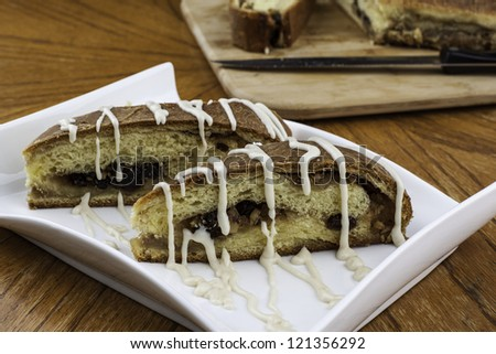 Nicely plated iced rain nut bread with loaf and knife in background on wood cutting board - stock photo
