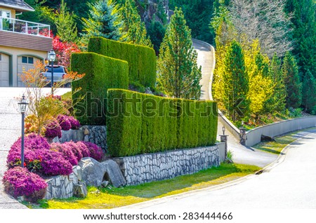 Nicely trimmed bushes, green fence and lowers and stones on different levels in front of the house, front yard. Landscape design. - stock photo