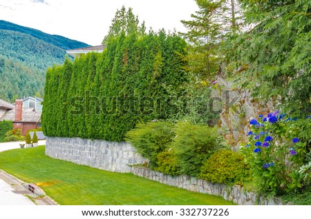 Nicely trimmed bushes, green fence, flowers and stones in front of the house, front yard. Landscape design. - stock photo