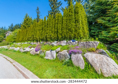 Nicely trimmed bushes, green fence  in front of the house, front yard. Keeps privacy and security. Landscape design. - stock photo