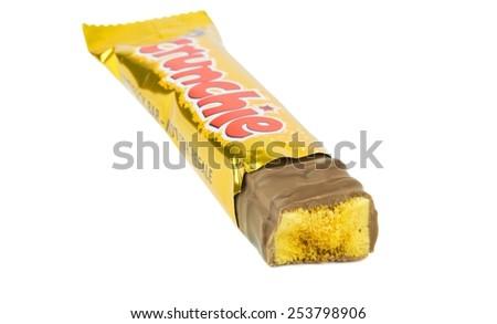 NIEDERSACHSEN, GERMANY FEBRUARY 17.02.2015: A single Cadbury crunchie chocolate bar broken showing honeycomb center on a white background - stock photo