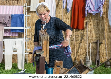NIEUWEHORNE, THE NETHERLANDS - SEP 27: Farmer woman demonstrating the use of a traditional washhub during the agricultural festival Flaeijel on September 27, 2014, the Netherlands