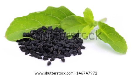 Nigella or black cumin with a medicinal tulsi leaves - stock photo