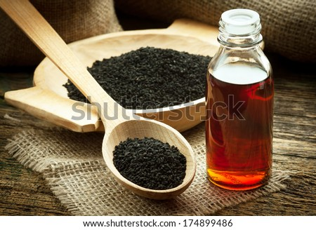 Nigella sativa (Black cumin) on wooden spoon and essential oil. Real oil from nigella looks like dark honey - stock photo