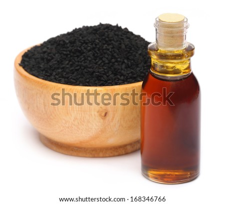 Nigella sativa or Black cumin with essential oil over white background - stock photo
