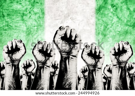 Nigeria Labor movement graphic concept, workers union strike concept with male fists raised in the air fighting for their rights and Nigerian national flag in out of focus background. - stock photo