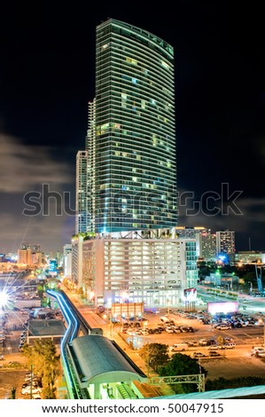 Night aerial view of a downtown apartment building in miami and metrorail station. - stock photo