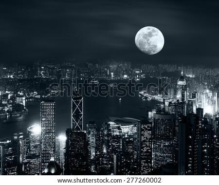 Night aerial view panorama of Hong Kong skyline at full moon night under cloudy sky - stock photo