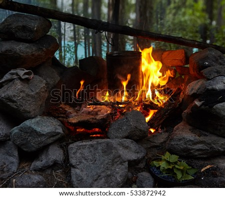 night bonfire at the shore of the river in a forest with bowler