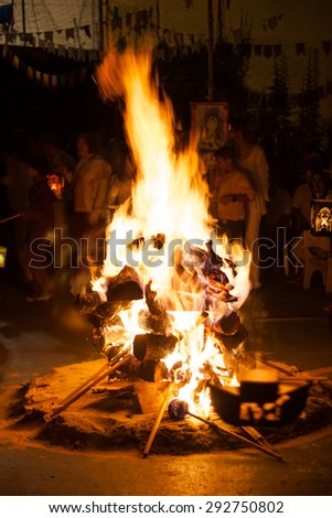 Night campfire with people surrounding on school party - stock photo