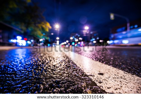 Night city after rain, the headlights of passing cars racing. Wide angle view of the level of the dividing line, in blue tones - stock photo