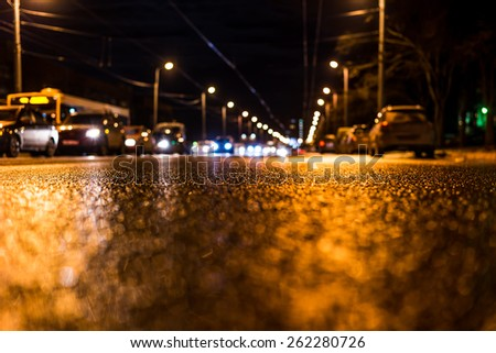 Night city after rain, view of the flow of cars from the road at the asphalt - stock photo