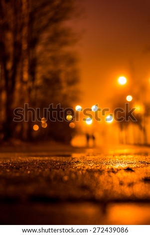 Night city alley with lanterns in the fog after rain and a couple of people walking on it. View from the level of asphalt, in yellow tones - stock photo