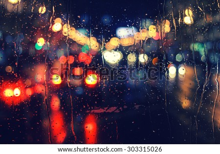 night city life through windshield: cars, lights and rain, vintage style photography