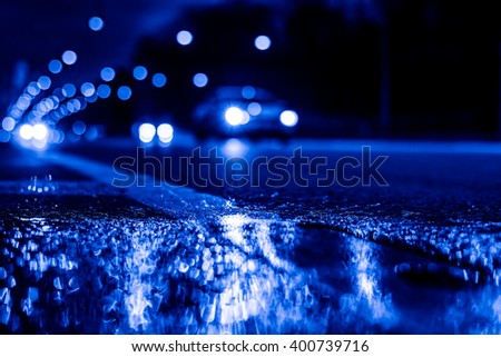 Night city lights reflected in a puddle, light from the headlights of approaching cars. Close up view from the level of the dividing line, image in the blue toning