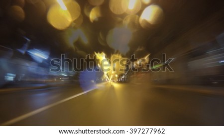 Night city time lapse driving. City, blurred motion, fast driving, rain. Camera in the front, starglow from the lights and blur motion - stock photo