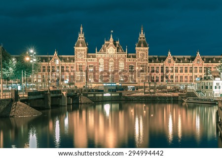 Night city view of Amsterdam canal and Centraal Station, Holland, Netherlands. Long exposure.. Toning in cool tones