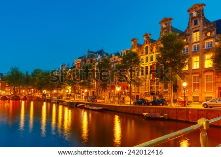 Night city view of Amsterdam canal, bridge, boats and bicycles, Holland, Netherlands.  - stock photo