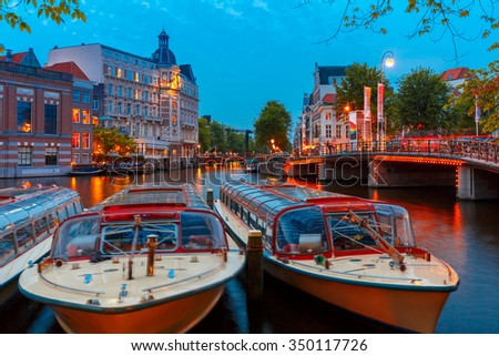 Night city view of Amsterdam canal, bridge, typical dutch houses and boats, Holland, Netherlands. - stock photo