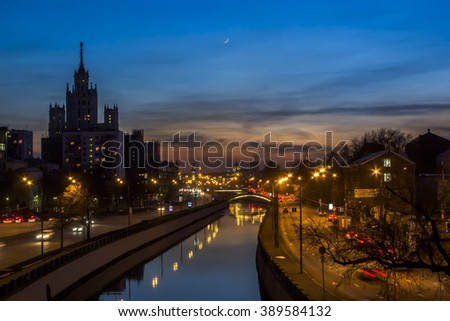 Night city: view of the river Yauza, sunset sky, new moon, bridge, the Traffic Trails  and the  high-rise building on Kotelnicheskaya embankment, Moscow, Russia. Soft focus. - stock photo