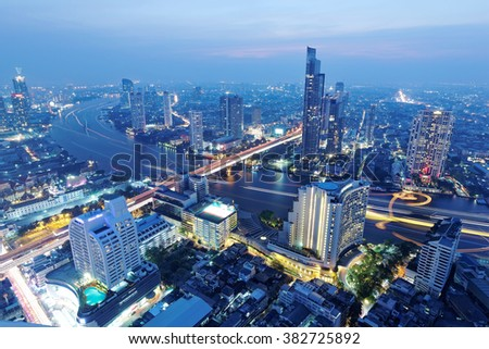 Night Cityscape of Bangkok in bird's eye view ~ Aerial panorama of Bangkok in evening twilight with busy traffic trails on Taksin Bridge over Chao Phraya River and skyscrapers along the riverside - stock photo