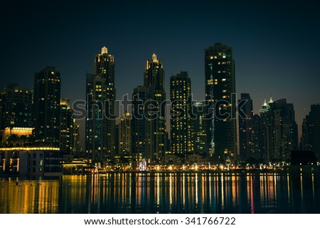 Night cityscape of Dubai city, United Arab Emirates. Reflections in the water. Filtered shot - stock photo