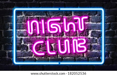 Night club neon sign on brick wall - stock photo