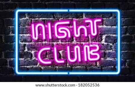 Night club neon sign on brick wall - stock photo