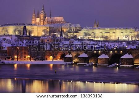 Night colorful snowy Prague gothic Castle with Charles Bridge, Czech republic - stock photo