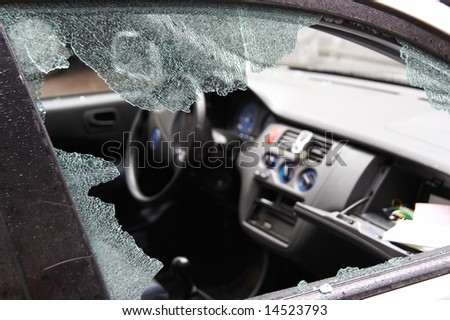 Night crime - the broken window of the car and abduction of things from a box on the forward panel - stock photo