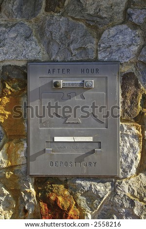 Night deposit box on weathered stone wall