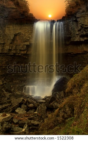 Night Falls, surreal effect created with Sunset on fifty foot waterfall under a Bridge called Ashgill Force in Northumberland England - stock photo