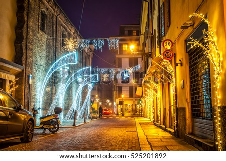 Night festive street decorated with lighting angels in Parma, Emilia-Romagna, Italy.
