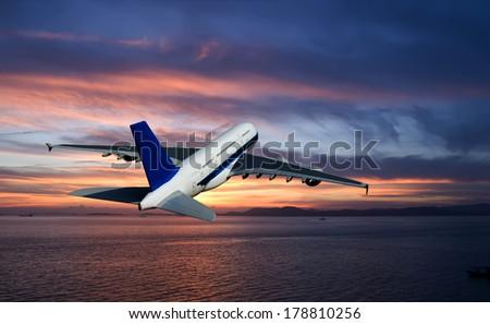 Night flight. Jet aircraft over the sea at dusk - stock photo