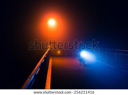 Night foggy city walk on a bridge with street light (toned) - stock photo