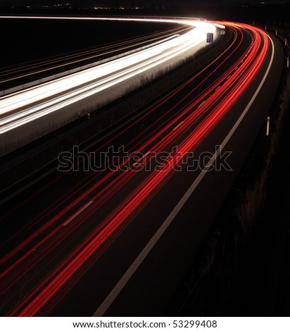 Night highway (Cars in a rush moving fast on a highway (speedway) at the nightfall - stock photo