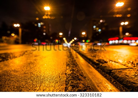 Night highway with rails, the glowing lights of approaching cars. Wide angle view of the level of the rails - stock photo