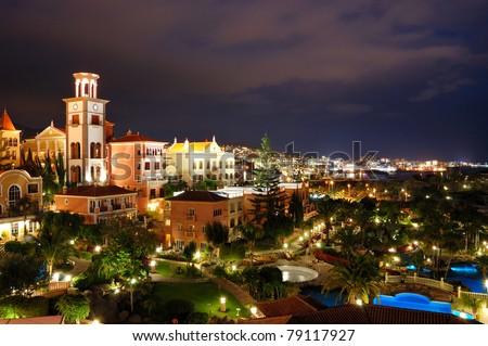 Night illumination of luxury hotel during sunset and Playa de las Americas at background, Tenerife island, Spain - stock photo