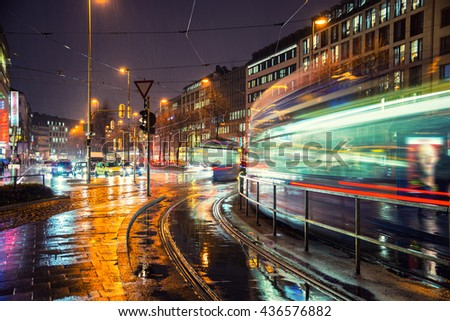 Night in Munich, Germany city center. Motion blurred trams and car traffic. Lights and illumination reflection during the heavy rain.