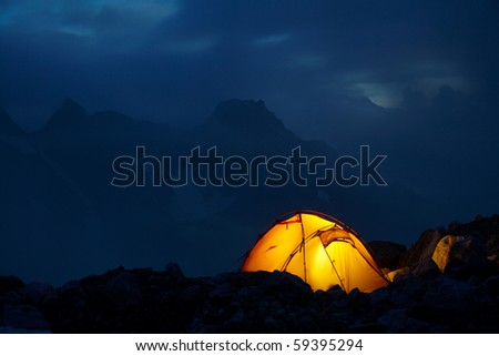 Night in the high mountains and orange tent between stones - stock photo