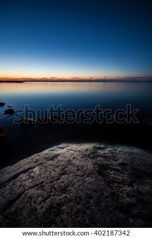 Night lake landscape and rock - stock photo