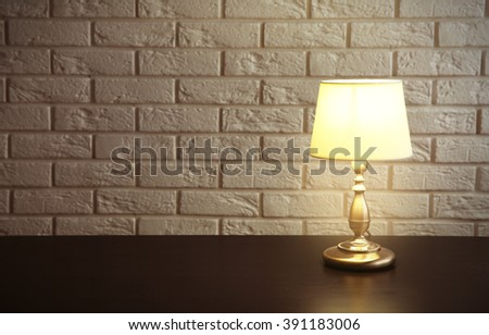 Night lamp on the desk on white brick wall background