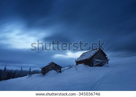 Night landscape. Winter in mountain village. Light in windows of wooden houses. Path in snow. Carpathians, Ukraine, Europe - stock photo