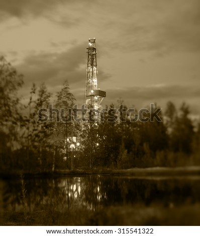 Night landscape with the drilling rig. Selective focus, shallow depth of field. - stock photo