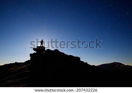 Night landscape with the starry sky. Moonlight over a man standing on a rock  - stock photo