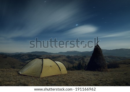 Night landscape with tourist tent in the mountain village. Carpathian mountains, Ukraine, Europe - stock photo