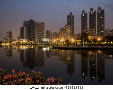 Night light with modern building and flower foreground in the park beside lake at Bangkok, Thailand (Benchakitti Park)